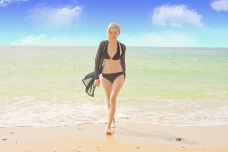 Young beautiful girl walking along the sea in a swimming suit  Stock Photo
