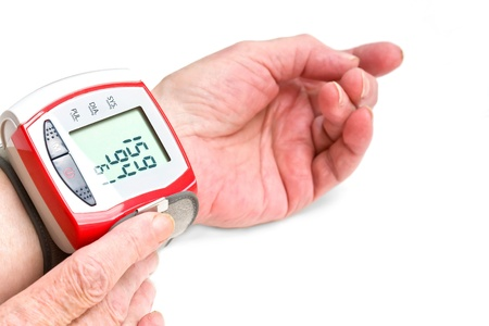 The hands of an old woman measuring blood pressure with a wrist meter  photo
