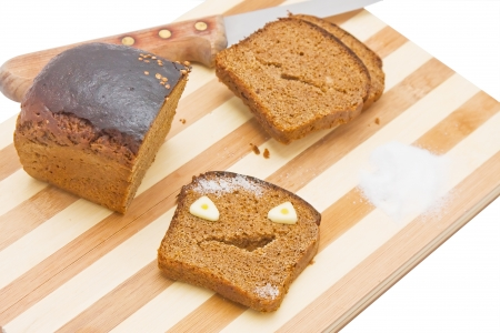 Sliced bread with the chunk and knife on a kitchen board, with a bread-garlic monster Stock Photo - 14360830