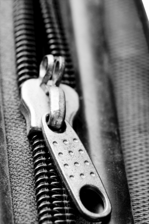 Closeup on a metal pull-tab of a black plastic suitcase photo