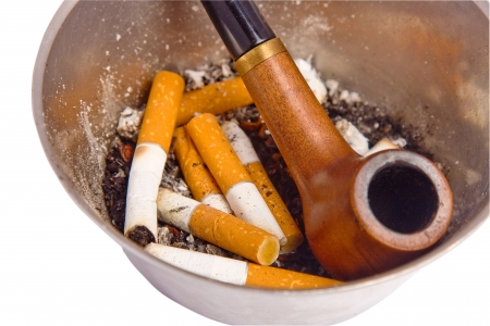 Closeup on ashtray with cigarette butts and a pipe photo