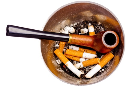 Dirty ashtray with cigarette butts, ashes, and a pipe