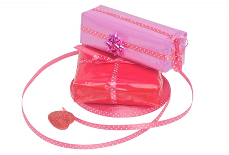 Set of wrapped gifts with pink ribbon and a decoration heart isolated over white photo