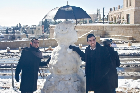 JERUSALEM - JANUARY 10: Jewish religious people in Jerusalem with a snowman constructed after a heavy snowfall in Jerusalem, Israel on January 10, 2013 Stock Photo - 17262500