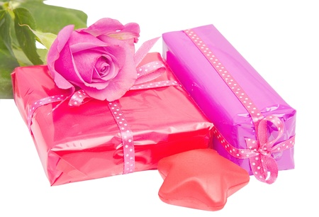Set of wrapped birthday gifts with a decoration star and a rose isolated photo