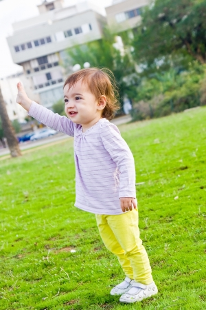 Cute toddler girl waving goodbye standing on a green lawn photo