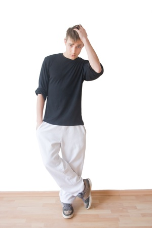 preoccupied: Handsome young man standing against a white wall with preoccupied expression Stock Photo