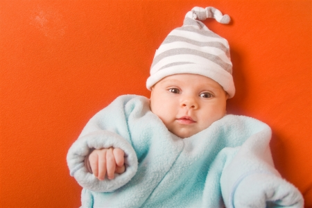 Adorable female baby in striped hat on orange poof photo