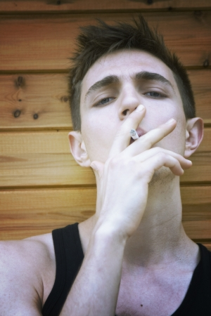 Close portrait of a young man smoking a cigarette (retrocold toning)