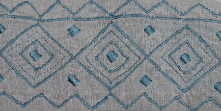 Closeup on grey fabric tissue with embroidered blue pattern photo