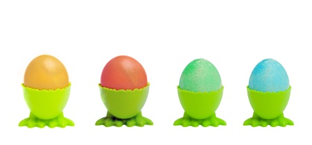 A row of colorful Easter eggs in green cups photo