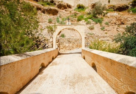 ordeal: Stone bridge and a gate archway with Greek Orthodox Church symbol