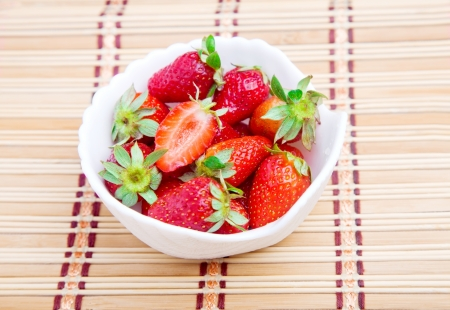 twinning: Bowl of frersh strawberries on the kitchen straw mat