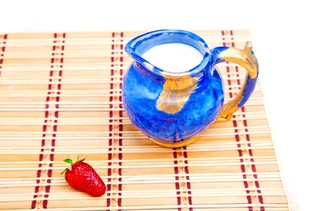 twinning: Milk jar and single strawberry on straw mat Stock Photo