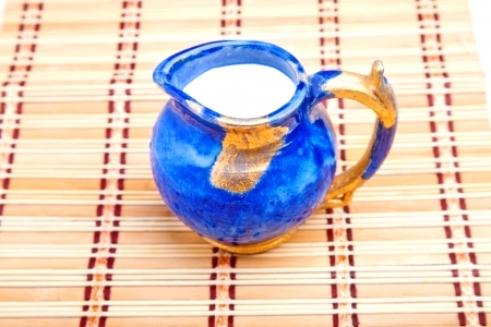 twinning: Blue milk jar on the straw kitchen mat Stock Photo
