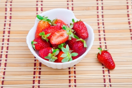 twinning: Strawberries in white bowl on straw mat