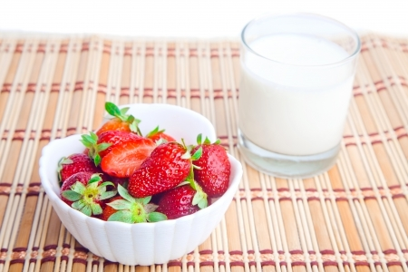 twinning: Bowl of strawberries and glass of milk on straw mat