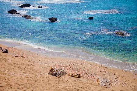 splutter: Sandy beach with broken shells near azure sea Stock Photo
