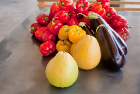 A selection of vegetables and fruit  pamelo, sweet peppers, and marrow pumpkin  on a metal table Stock Photo