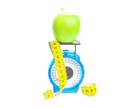 unattached: Fitness diet concept with green apple on the scale isolated on white