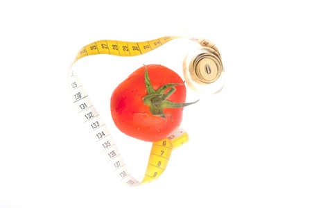 Fresh tomato with water drops and yellow centimeter isolated on white