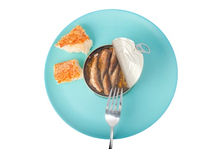 Eating Sprats with white bread on a blue plate  isolated  photo