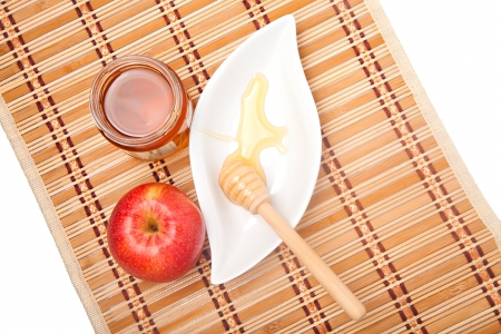 Jar of honey with red apple on a straw kitchen mat photo
