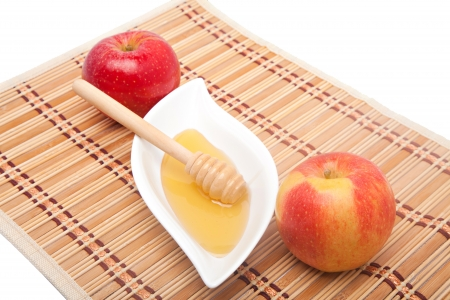 Two apples and honey on a straw kitchen mat photo