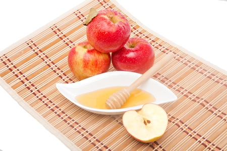 Sliced apple and honey dipper with three red apples on straw mat photo