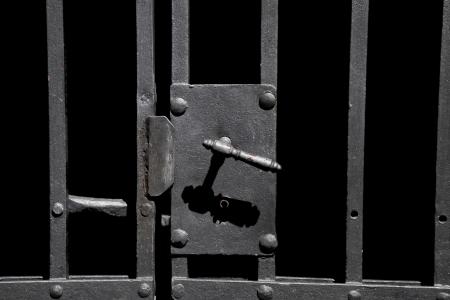 Closeup on old rusty metal bar door with old-fashioned lock Stockfoto