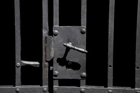 Closeup on old rusty metal bar door with old-fashioned lock Stock Photo