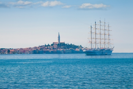 Sea landscape with sailing vessel and general view of medieval town photo
