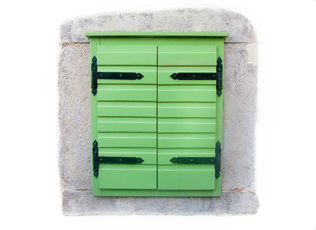 Wood window shutters with vintage metal hinges freshly painted green  photo