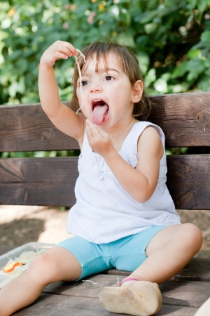 Cute little girl swallowing spaghetti with funny expression