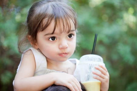 sholders: Cute little girl riding her mothers sholders with a glass of juice in hand Stock Photo