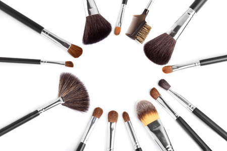 Circle of professional makeup brushes over white background photo