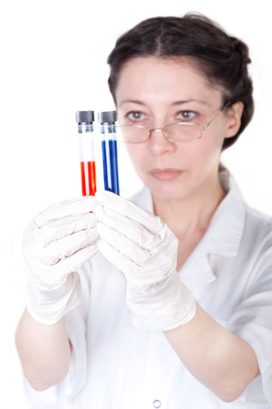 Test tubes with different results are studied by a female lab researcher (focus on the tubes) photo