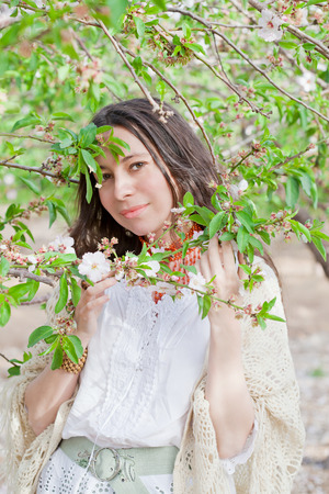 Beautiful female portrait in spring tree blossom photo