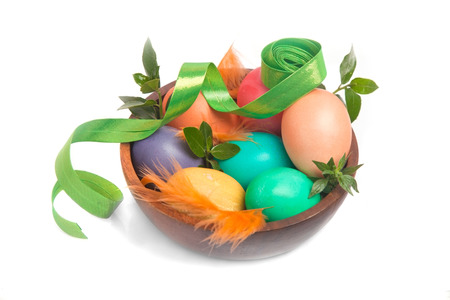 Rainbow-colored Easter eggs with greens and decoration ribbon in wooden bowl over white (with shadow) photo