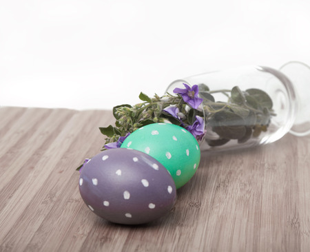 Two dotted eggs on wooden surface and flowers in a glass (dulled colors, focus on the mint egg) photo
