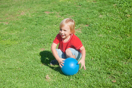 wil: A happy boy wil blue ball on a green lawn Stock Photo