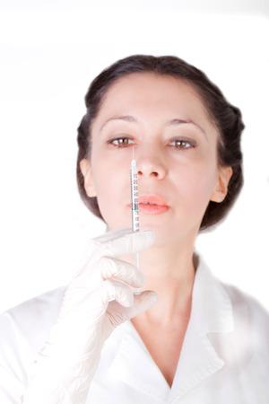 Female nurse checking empty syringe (isolated over white)