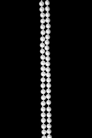 Double thread of fashion pearls over black background vertical photo