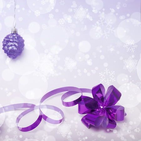 Square Christmas background in lilac tint with a ribbon bow, decoration cone and snowflakes photo