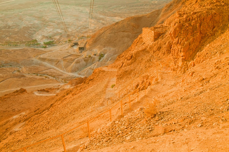 ascend: View of the the valley laying under the Snake Path ascend to Massada Fortress (Israel) at dawn (unusual desert sunrise lighting) Stock Photo