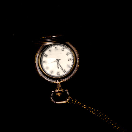 watch over: Vintage pocket watch over black background