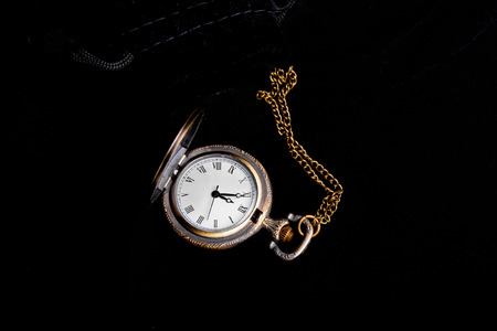 five to twelve: Vintage watch showing five minutes to twelve over black background Stock Photo