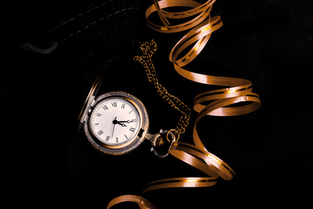 five to twelve: Waiting for the New Year - vintage watch showing five to twelve and decoration ribbon over black