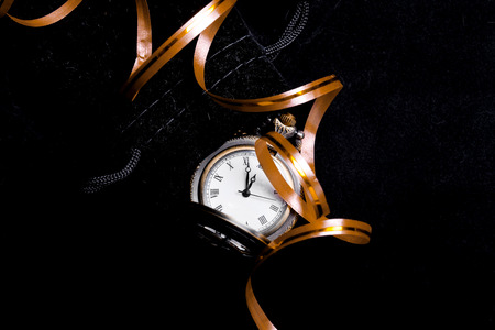five to twelve: Waiting to party concept - the pocket watch showing five minutes to twelve with decoration ribbon (New Years concept)