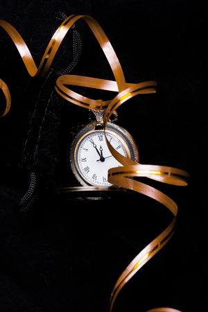five to twelve: Vintage pocket watch showing five minutes to twelve on black background with golden decoration ribbon (vertical)